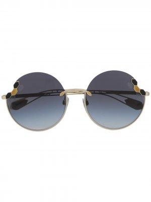 Солнцезащитные очки в круглой оправе Bvlgari. Цвет: золотистый